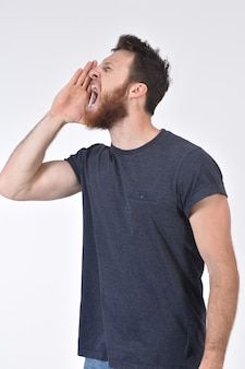 Man putting a hand in mouth and is screaming on white
