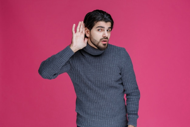 Man putting hands over his ears because of volume.