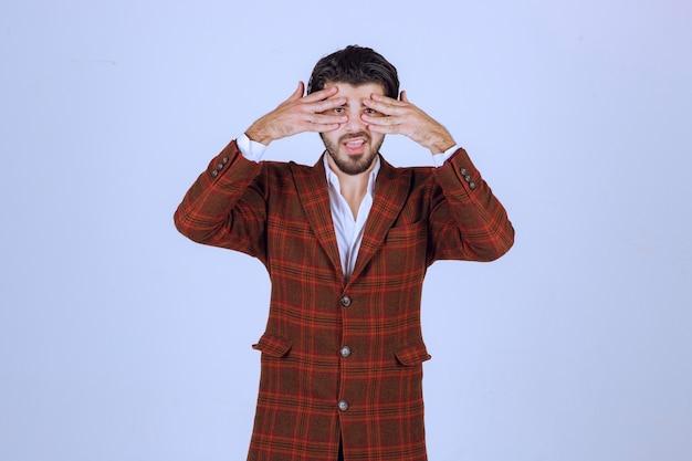 彼の顔に手を置き、目のサインを作る男。