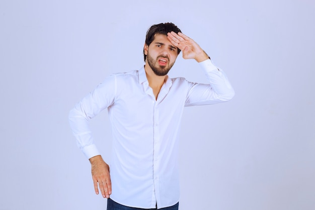Man putting his hand to his forehead and looking forward.