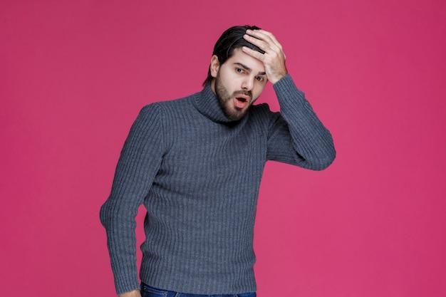 큰 실수를 저질렀거나 피곤함을 느끼면서 손으로 머리를 쓰는 남자.