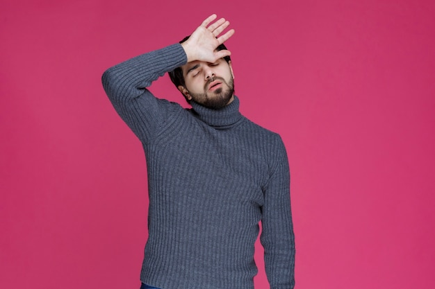 彼は大きな間違いをしたか、疲れを感じているので、手で頭を置く男。