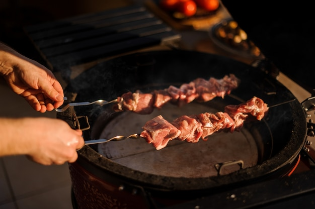 Man putting a large meat pieces on the skewer to the grill