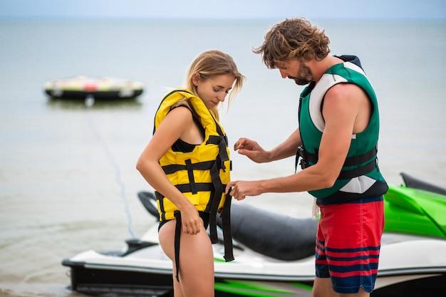 Мужчина надевает спасательный жилет на женщину, чтобы кататься на водном скутере, летние каникулы, активный спорт, безопасность