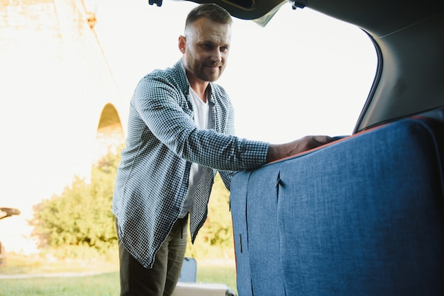 자동차 트렁크에 짐을 넣는 남자.