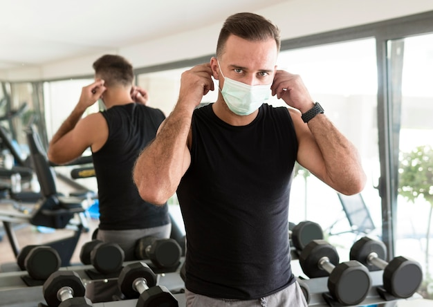 Man putting on medical mask at the gym