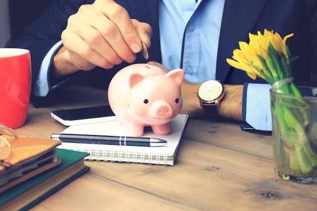 テーブルの上の貯金箱にお金を入れている男