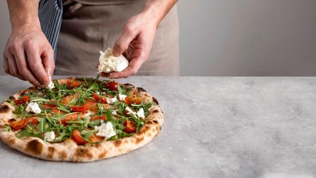 Мужчина кладет моцареллу на тесто для запеченной пиццы с ломтиками копченого лосося