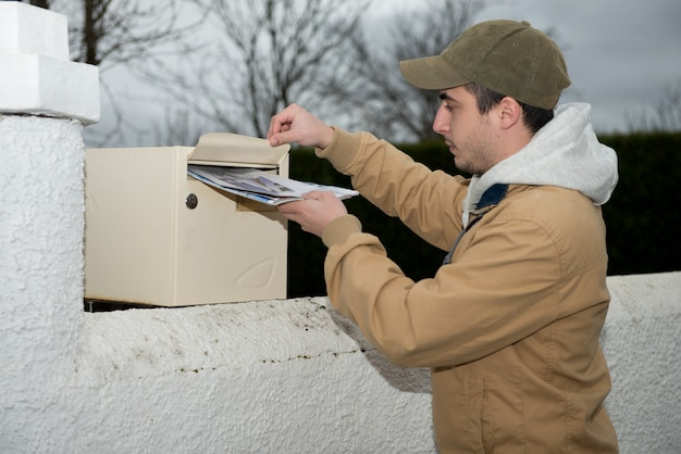 Man putting newspaper from the mailbox