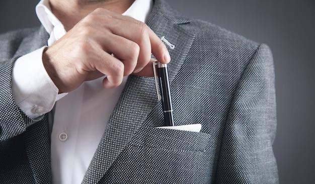 スーツのポケットにペンを置く男。