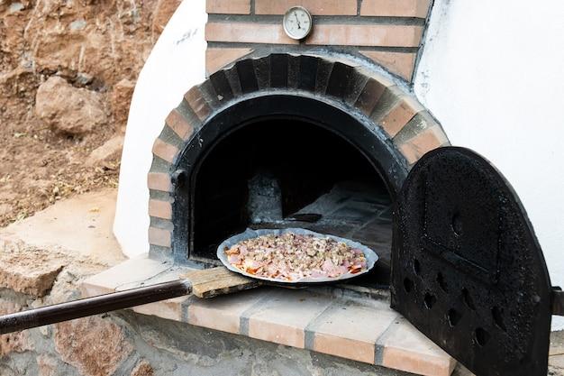 シャベル、背景と屋外で構築された手作りの白い塗られた木製オーブンにピザを置く男