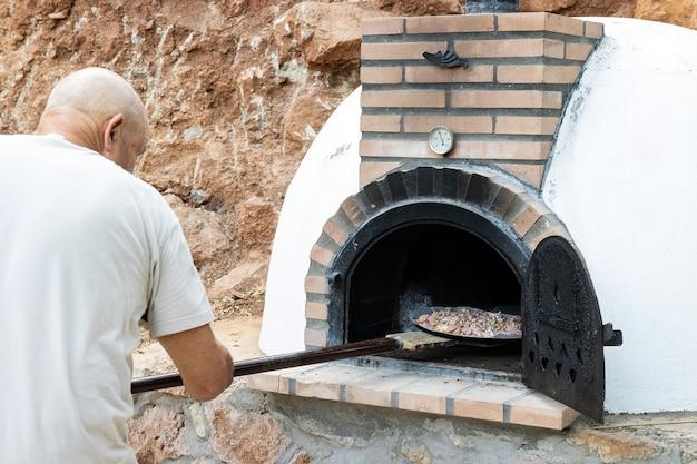 삽으로 야외에 지어진 수제 흰색 페인트 나무 오븐에 피자를 넣는 남자