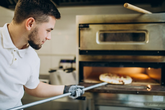 Man putting pizza in oven at pizzeria
