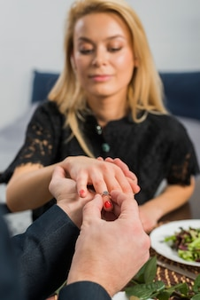 Man putting ring on woman finger at table