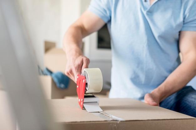 移動するためにそれを確保するためにボックスにスコッチテープを置く男