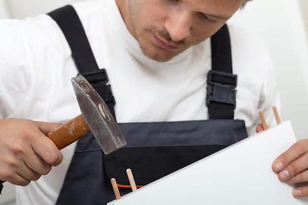 Человек собирает мебель самостоятельной сборки в новом доме крупным планом. сделай сам, дом и концепция перемещения