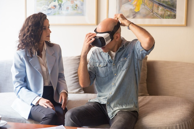 Man putting on vr headset for watching presentation