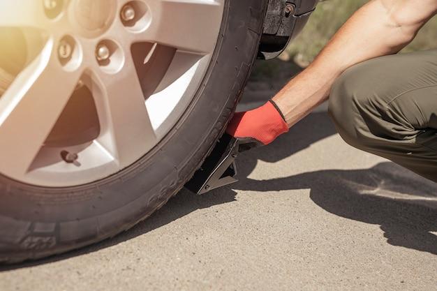 道路のクローズアップで車のホイールの下に車輪止めを置く男