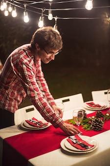 クリスマスの装飾でテーブルにワイングラスを置く男