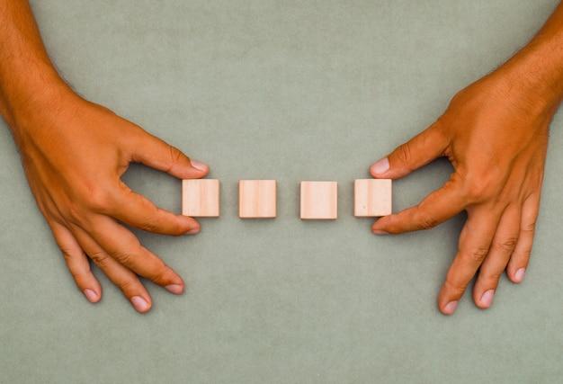 Человек ставит деревянные кубики в порядок.