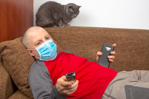 Man in quarantine at home with a medical mask on his face lies on the couch and watches the tv