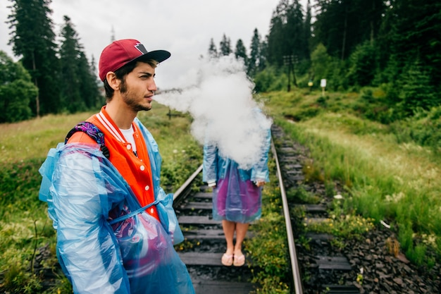 Man in raincoat blowing out clouds of smoke at railway