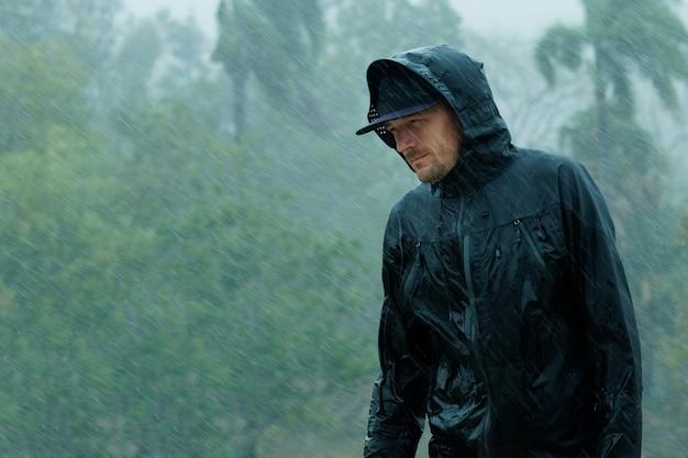 Man in raincoat under heavy tropical rain.