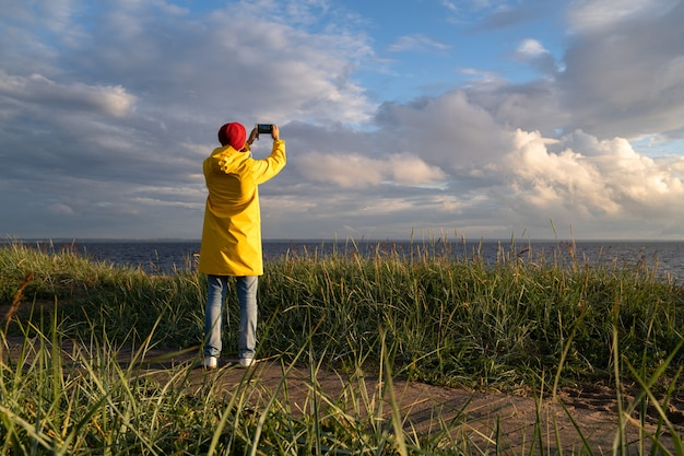 Man in raincoat standing on the beach and taking photos with smartphone
