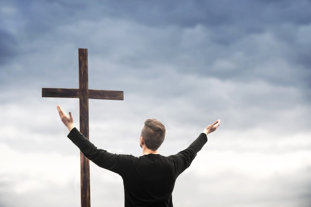 The man raised his hands and praises god. the man looks at the cross. man believes in god. hope in god