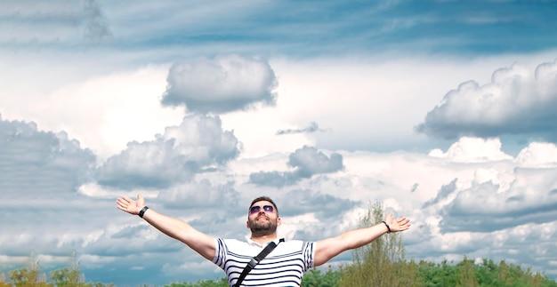 Мужчина поднял руки вверх на фоне неба с облаками улыбаясь счастливым