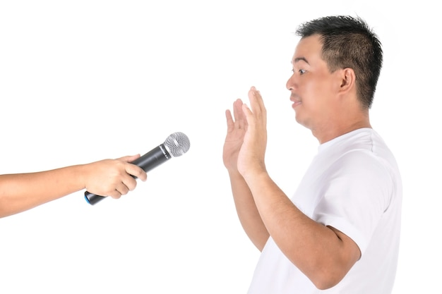 Man raises his hands to avoid speaking on microphone