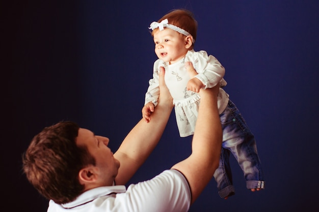 Man raises up little girl in jeans and white bow on her curly hair