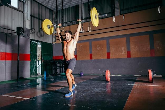 Man raising barbell in gym
