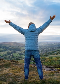 Man raising hands high and standing on top of mountain