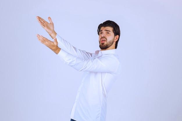 手を上げて上の何かを指している男。
