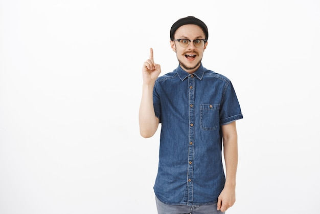 Man raising index finger in eureka gesture adding suggestion with focused calm expression standing in black beanie and blue shirt over gray wall