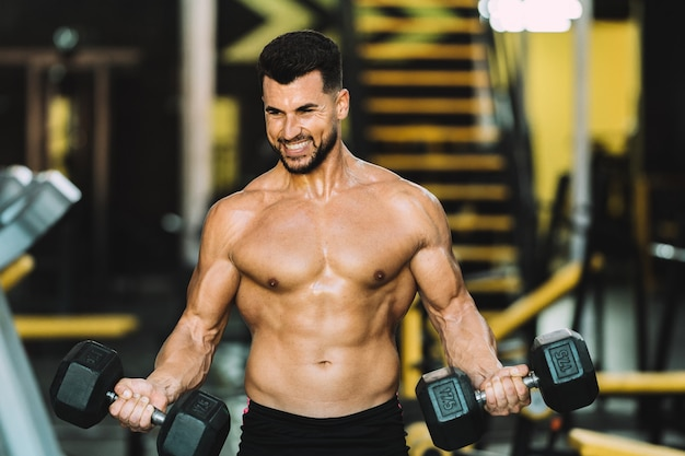 Man raising metallic dumbbells in a gym with expression of satisfaction