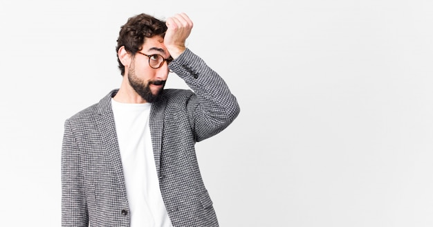 Man raising palm to forehead thinking oops, after making a stupid mistake or remembering, feeling dumb