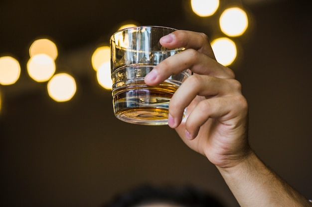 Man raising toast with whiskey glass on bokeh background