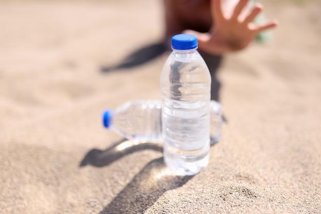 男は砂の上に立っている水のボトルに手を伸ばす