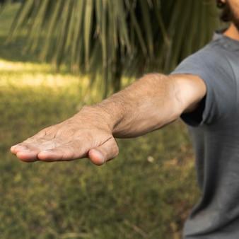 Мужчина протягивает руку во время занятий йогой на открытом воздухе