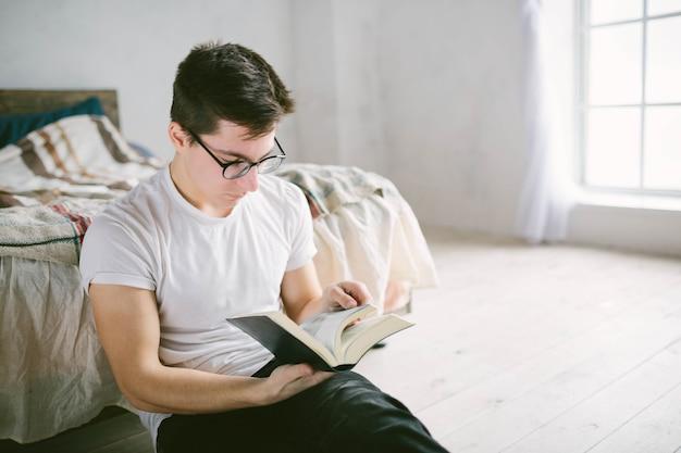 自宅のベッドで本を読んでいる男