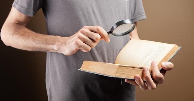 돋보기를 사용하여 책을 읽는 남자
