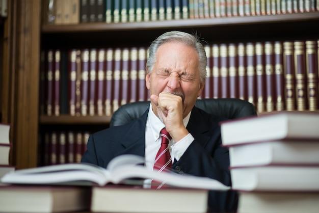 彼のスタジオの図書館で退屈な本を読んでいる男