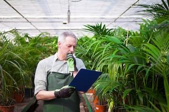 温室で文書を読んでいる男