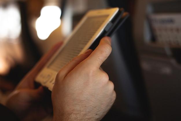 Человек читает электронную книгу в самолете