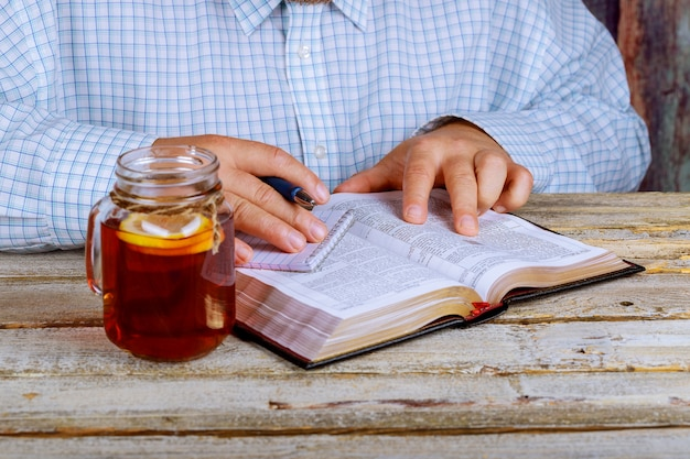 Man reading the bible as well as tea on the table