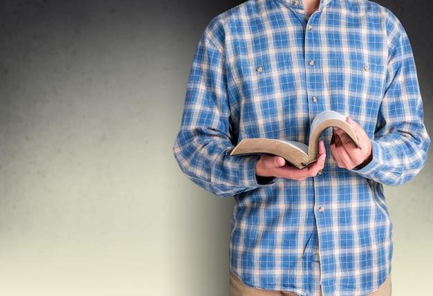 背景に聖書を読んでいる男