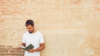 Man reading book against grunge wall