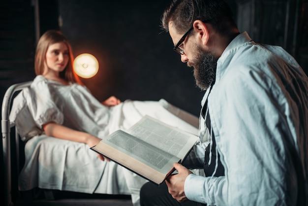 病院のベッドで病気の女性に対して本を読んでいる人